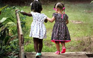 2 young girls walking together away from the camera.
