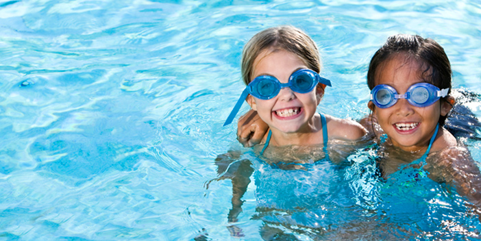 2 young girls with eye goggles in a swimming pool.