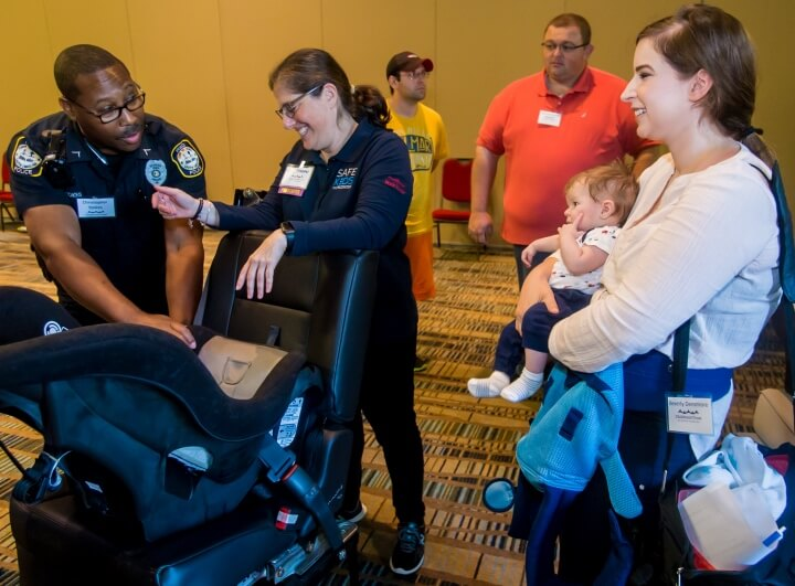 Technicians discuss getting infants safely in car seats.