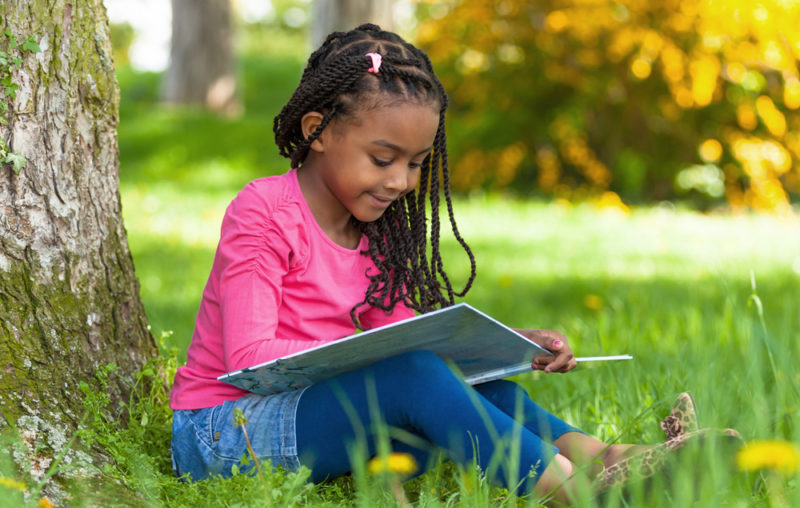 Cute-young-black-little-girl-reading-a-book