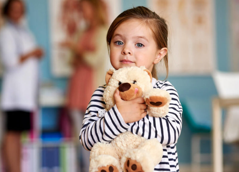 Young girl with stuffed animal doctors office