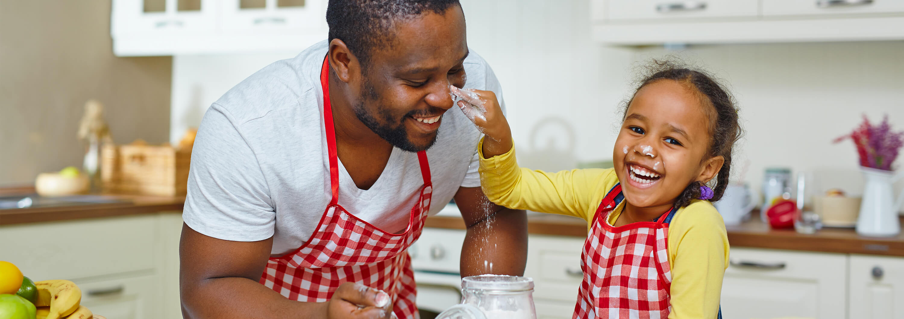 Father cooking with young daughter and laughing