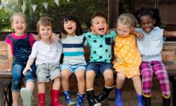Kindergarten-kids-friends-arm-around-sitting-smiling