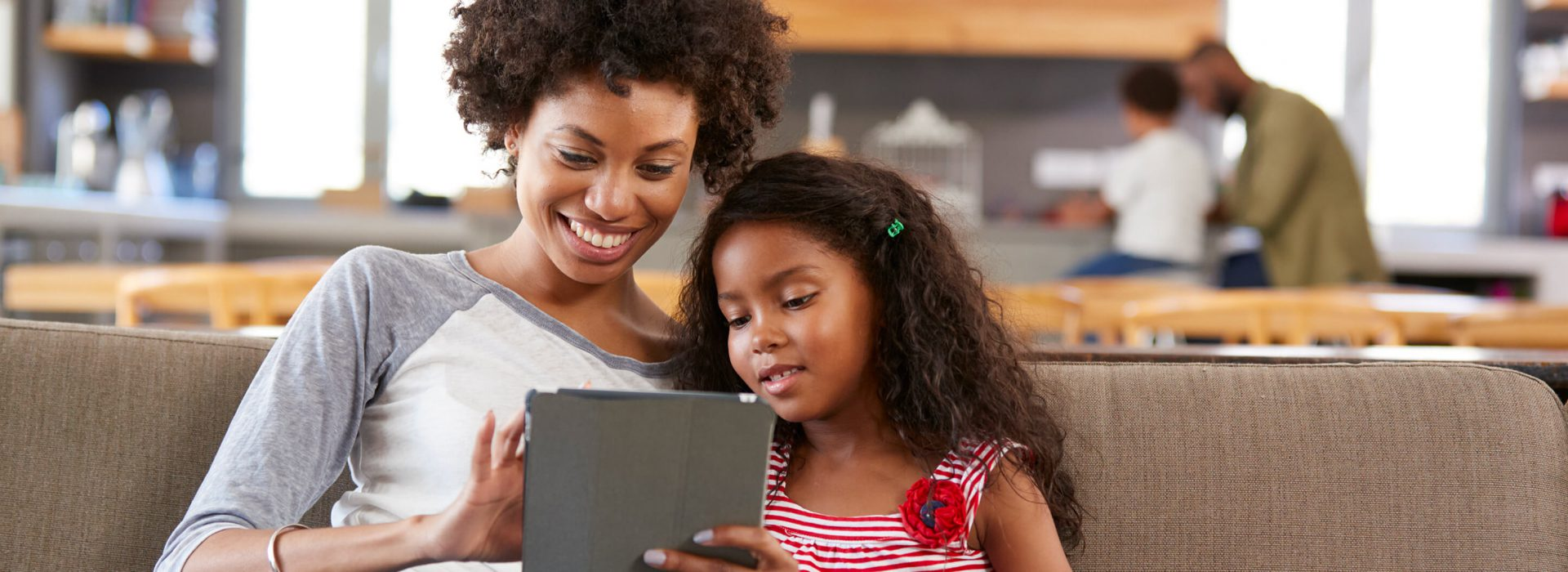 Mother-and-daughter-with-tablet-on-couch