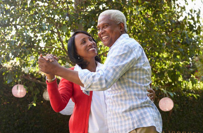 Senior black couple dancing in their back garden