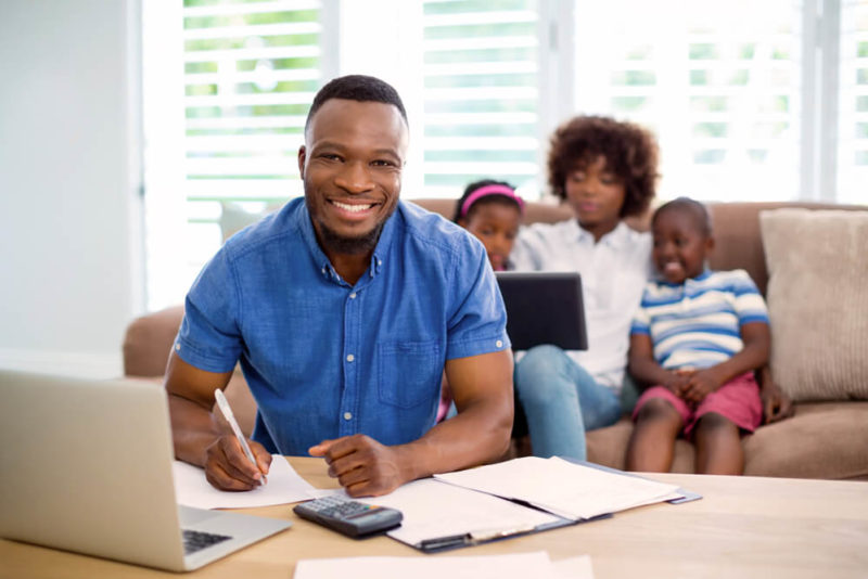 Smiling man calculating bills at home