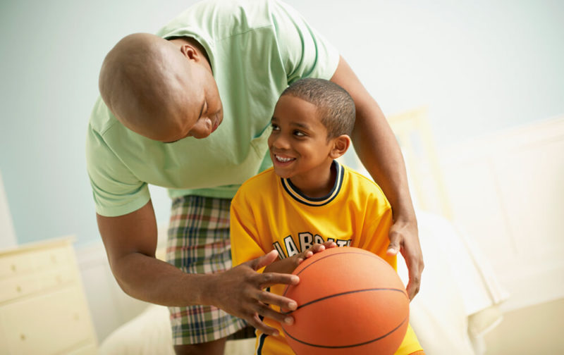 Father-helping-son-with-basketball