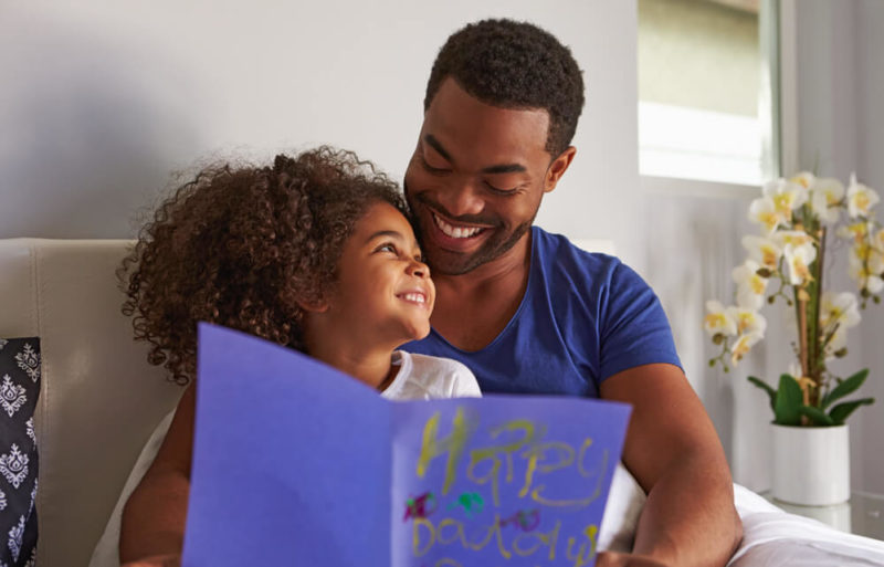 Happy-dad-and-daughter-in-bed-with-card-on-birthday