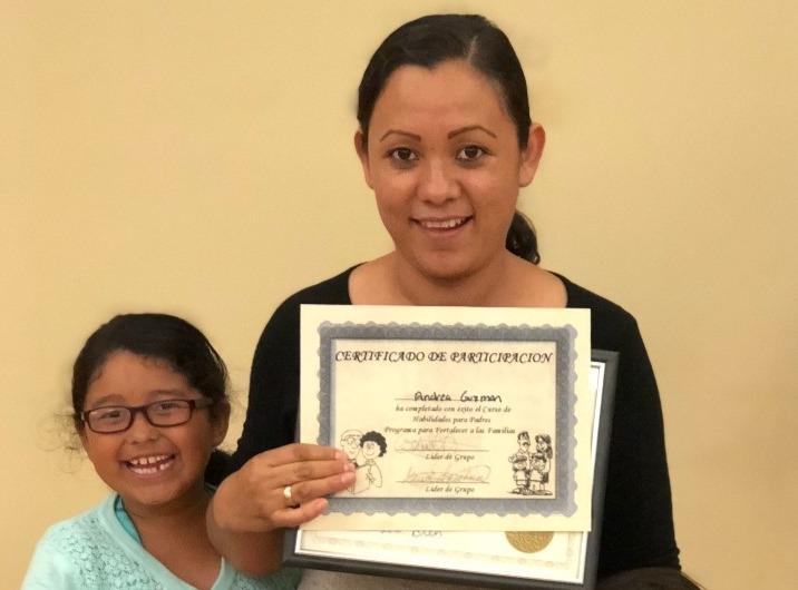 Andrea Guzman displays graduation certificate