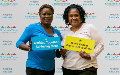Attendees-pose-with-signs-in-front-of-Childrens-Trust-banner