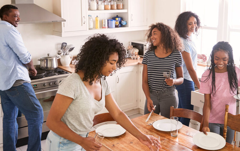 Family-With-Teenage-Daughters-Laying-Table-For-Meal-In-Kitchen