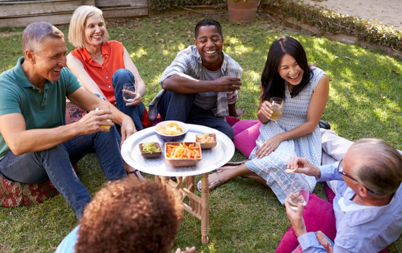 Group-Of-Mature-Friends-Enjoying-Drinks-In-Backyard-Together