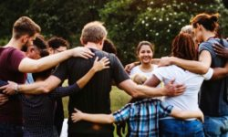 Group-of-people-huddle-together-in-the-park