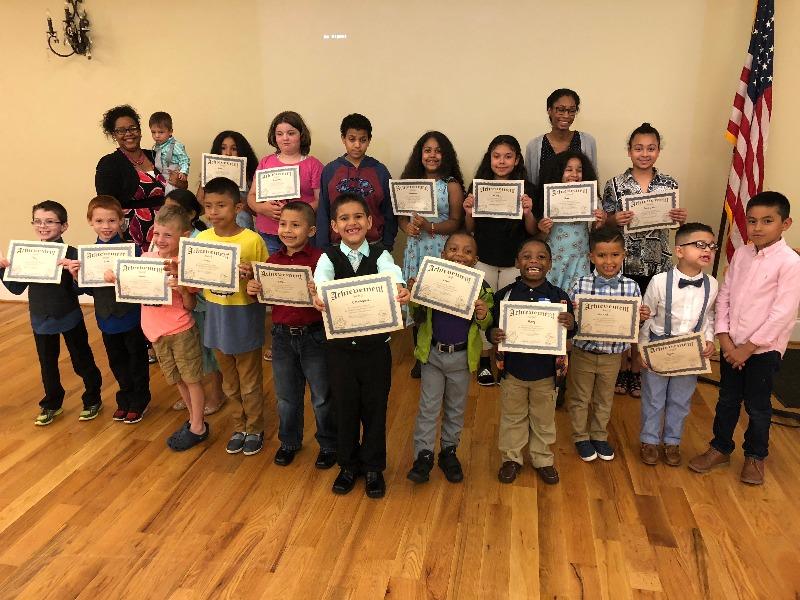 Children holding graduation certificates at SFP ceremony