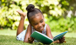 Little-girl-reading-a-book-at-park