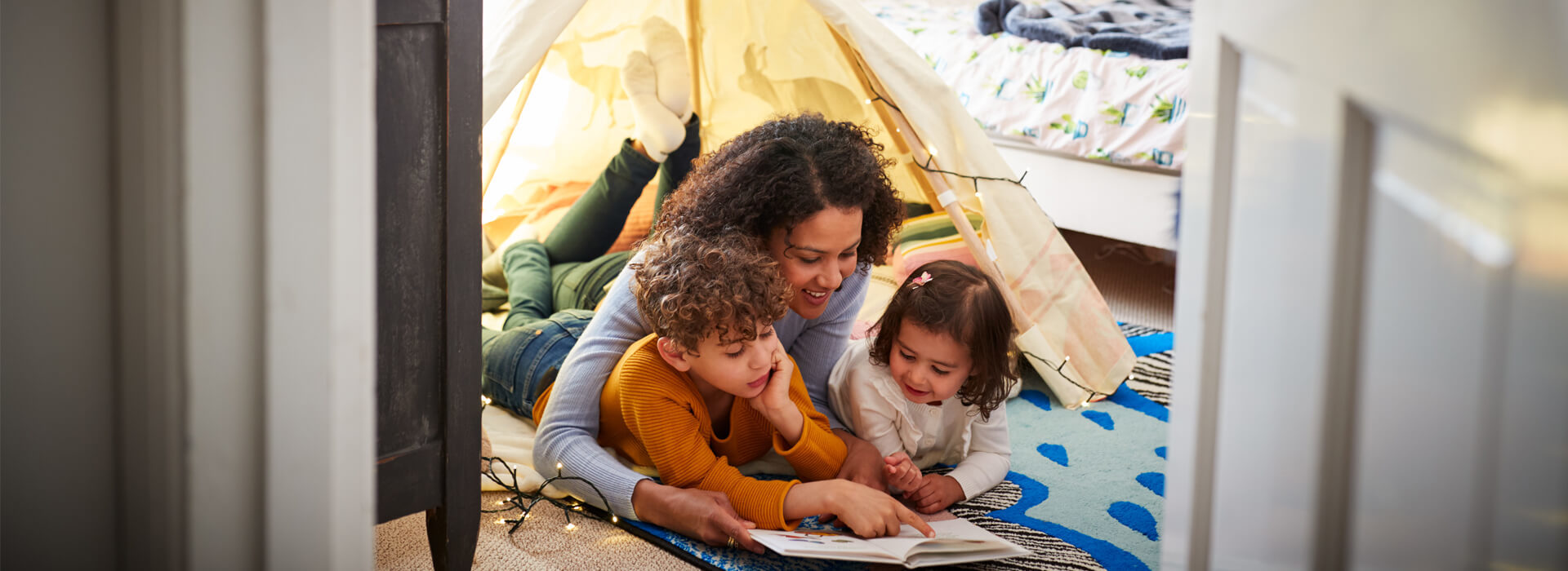 Mother under tent reading to her kids