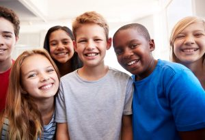 Portrait-Of-Smiling-Male-And-Female-Students-In-Grade-School-Classroom