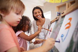 Teacher-at-school-helping-children-in-art-class