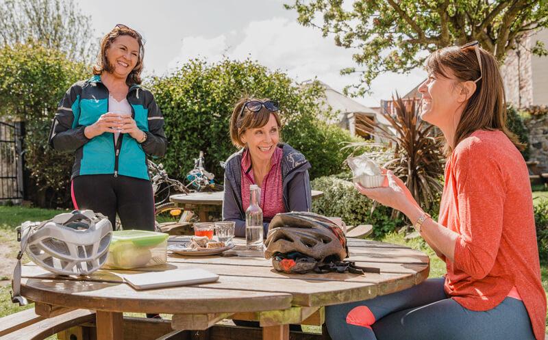 Women talking outside at table during bike ride break.