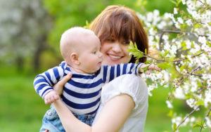 Young mother holding baby outside next to a blooming tree.