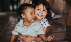 Young sister hugging her younger brother